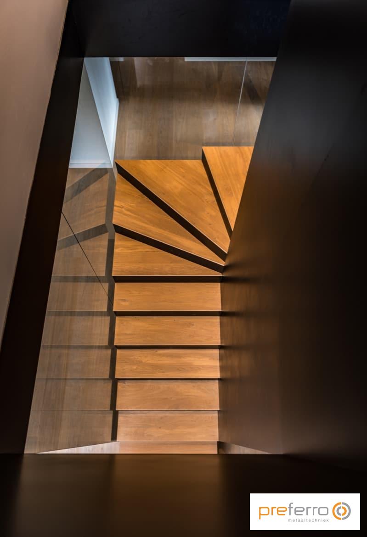Bovenaanzicht trap met houten treden in glazen trappenhuis